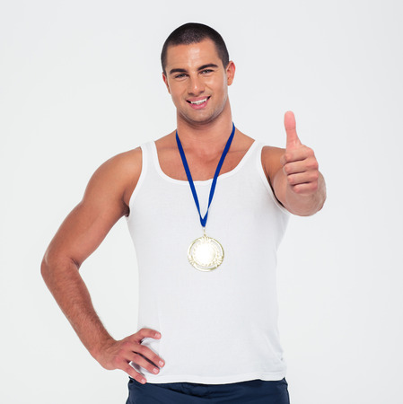 winner man: Portrait of a smiling man with gold medal showing thumb up isolated on a white background
