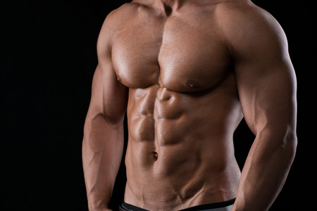 boy  naked: Closeup portrait of a muscular male chest on black background Stock Photo