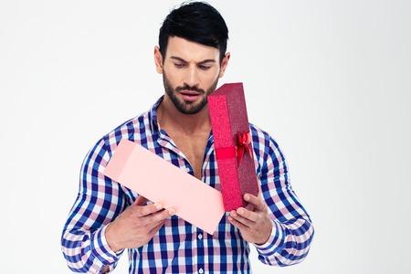 Portret van een jonge man opening geschenk doos geïsoleerd op een witte achtergrond