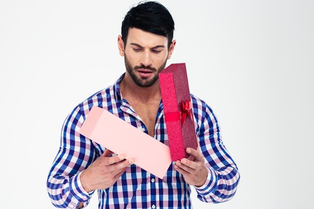 Portrait of a young man opening gift box isolated on a white background