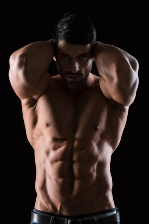 boy  naked: Portrait of a strong muscular man posing on black background