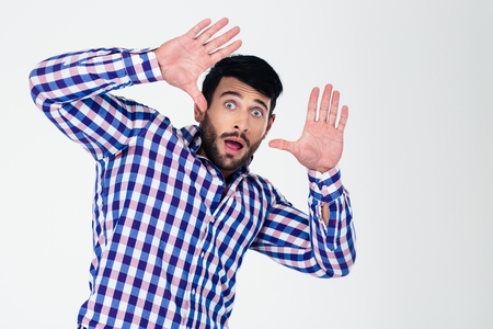 cease: Portrait of a scared man with raised hands up isolated on a white background Stock Photo