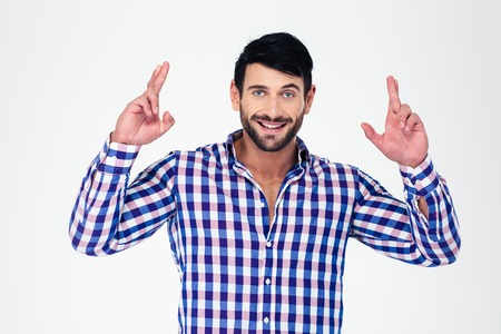 crossed fingers: Portrait of a happy man standing with crossed fingers isolated on a white background