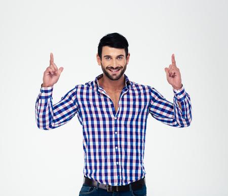 dedo apuntando: Retrato de un feliz hombre dedos apuntando hacia arriba en copyspace aislado en un fondo blanco Foto de archivo