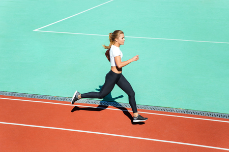 arena: Portrait of a young fitness woman running at stadium Stock Photo