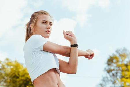 fitnes: Portret van een fitness-vrouw doet warming-up oefeningen in openlucht