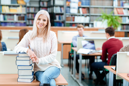 erudition: Portrait of a happy female student sitting on the desk with pile of books in university library and looking at camera