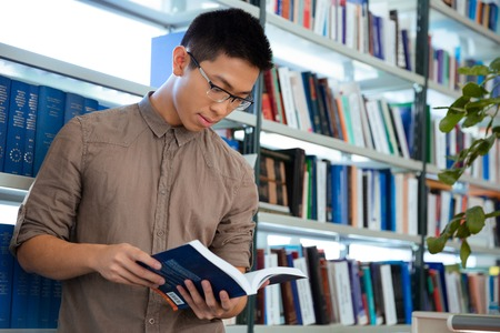 reading: Portrait of a young asian man reading book in library Stock Photo