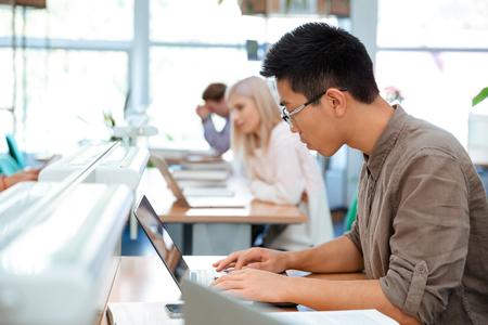 biblioteca: Retrato de un estudiante utilizando portátil en la biblioteca de la universidad