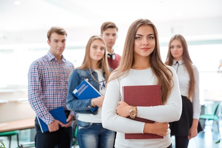 classmates: Portrait of a young female student standing in classroom with classmates on background Stock Photo