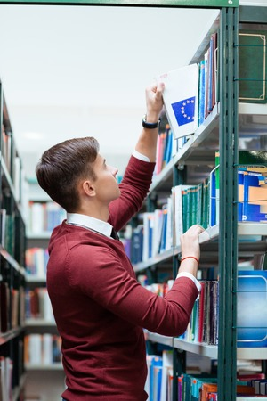 univercity: Young boy is taking a book about the European Union from the bookcase in the library Stock Photo