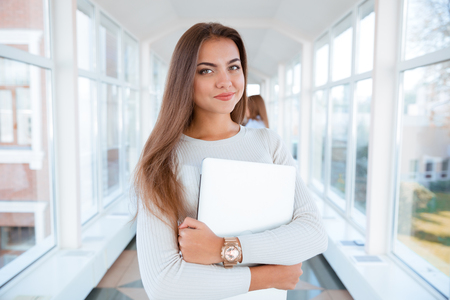 Portrait of a young beautiful woman standing in university hall and looking at camera Фото со стока