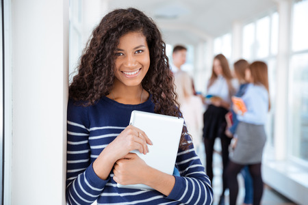 classmates: Portrait of a smiling female student standing in university hall with classmates on a background