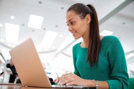 kavkazský: Portrét šťastná studentka pomocí přenosného počítače v univerzitní