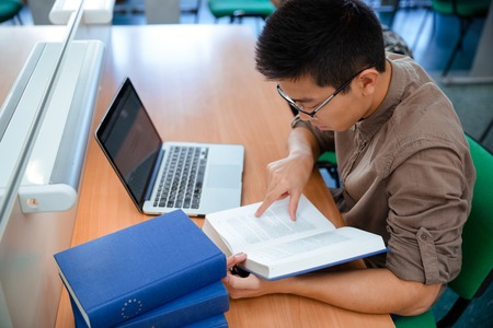 reading book: Portrait of asian male student reading book in university Stock Photo