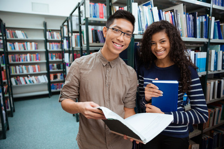 Portrait of a happy students searching books in library Stock Photo