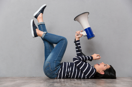 young woman legs up: Young beautiful happy smiling woman lying with legs up and speaking in megaphone Stock Photo