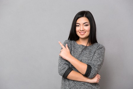 looking away from camera: Portrait of a happy woman pointing finger away and looking at camera over gray background