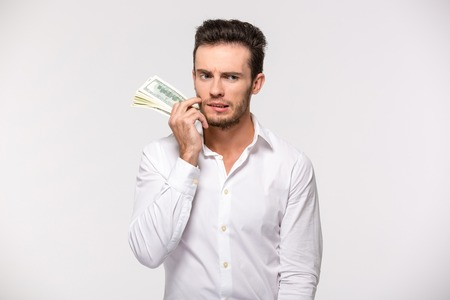 dinero: Portrait of a pensive man holding dollar bills isolated on a white background