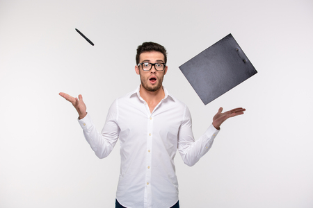 staring at the camera man: Portrait of a funny businessman throwing clipboard and pen into the air isolated on a white background