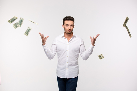 Portrait of a young man throwing money in the air isolated on a white background Foto de archivo
