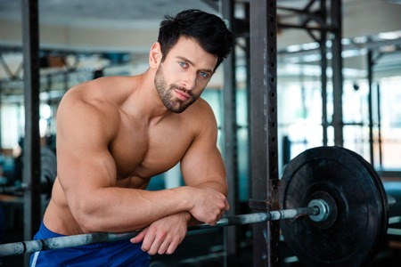 Portrait of a muscular male bodybuilder looking at camera in fitness gym