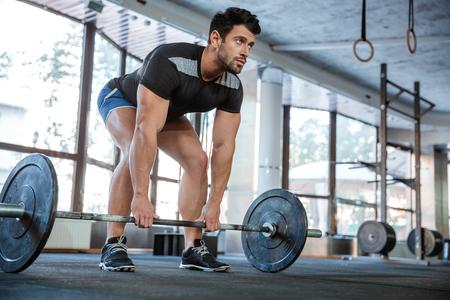 muscular: Athlet con pantalones cortos azules y negro camiseta de elevaci�n gran mancuerna Foto de archivo