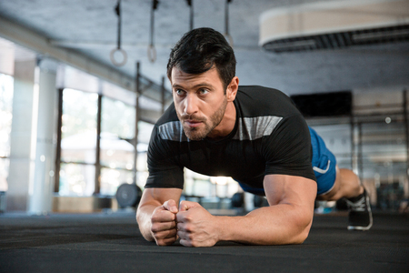 Athlet bär blå shorts och svart t-shirt gör statisk träning Stockfoto