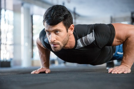 handsome young athletic: Portrait of a fitness man doing push ups in gym Stock Photo