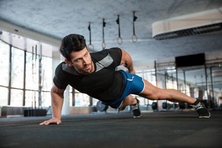 Portrait of a handsome man doing push ups exercise with one hand in fitness gym Standard-Bild