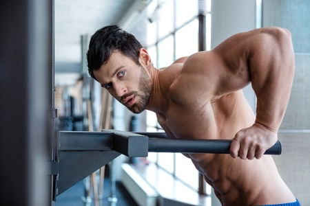 musculation: Portrait of a muscular man workout on parallel bars in fitness gym and looking at camera