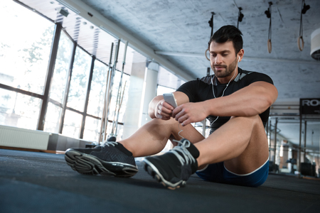 sports club: Athlet wearing b?ack sneakers sitting on the floor in gym and using cellphone Stock Photo