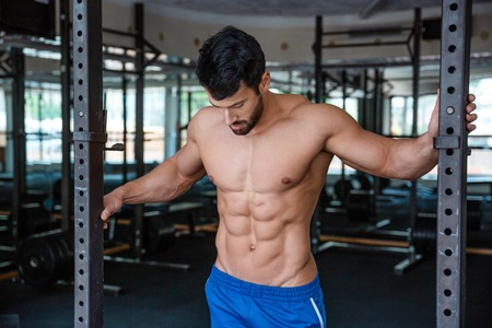 naked male body: Portrait of a handsome male bodybuilder standing in fitness gym Stock Photo