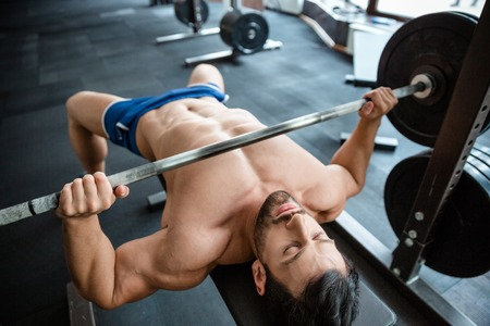 gym: Portrait of a handsome muscular man doing bench press in fitness gym Stock Photo