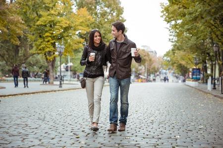 personas abrazadas: Retrato de una pareja joven y sonriente con café para caminar al aire libre en la vieja ciudad europea