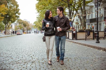 コーヒー野外を歩いている、古いヨーロッパの都市で、幸せなロマンチックなカップルの肖像画