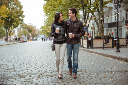 Portrait of a happy romantic couple with coffee walking outdoors in old european city