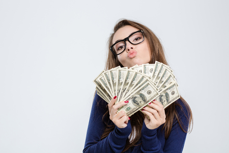 win: Portrait of a young woman holding bills of dollar and kissing on camera isolated on a white background