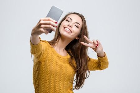 白い背景で隔離のスマート フォンで selfie 写真を作って笑顔のかわいい女性の肖像画