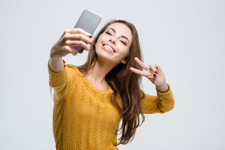 ?  ?    ?  ?    ?  ?    ?  smiling: Retrato de una mujer linda sonriente haciendo selfie foto en el smartphone aislado en un fondo blanco Foto de archivo