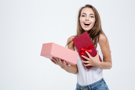 Portrait of a cheerful woman opening gift box isolated on a white background Stockfoto
