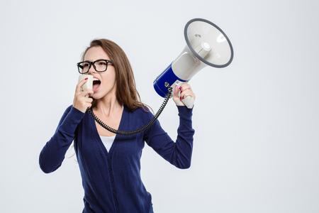 megafono: Retrato de una mujer joven que grita en el megáfono aislado en un fondo blanco
