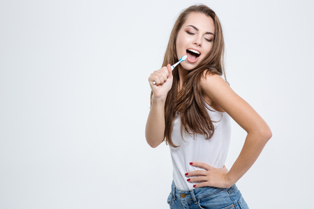 Portrait of a happy woman cleaning her teeth with toothbrush isolated on a white background