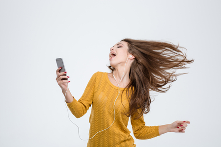 smiling girl: Portrait of a cheerful cute woman listening music in headphones and dancing isolated on a white background