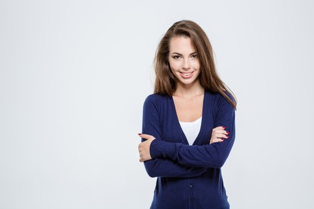 the caucasian beauty: Portrait of a smiling charming woman standing with arms folded and looking at camera isolated on a white background