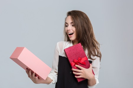 mujer elegante: Retrato de una caja de regalo de la apertura de negocios alegre sobre fondo gris Foto de archivo