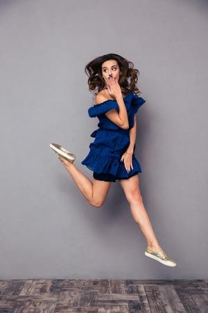 expresion corporal: Retrato de un salto de la mujer divertida y cubriendo su boca sobre fondo gris Foto de archivo