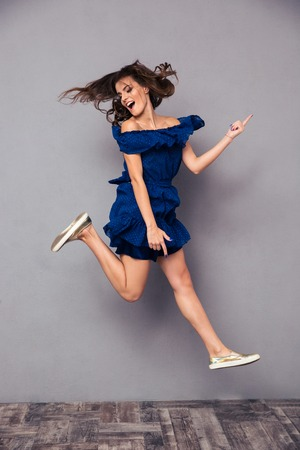 Portrait of a funny cheerful woman jumping on gray background Stockfoto