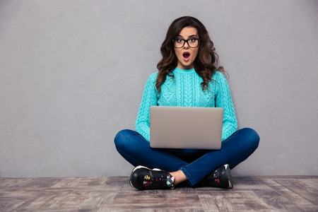 Portrait of shocked woman sitting on the floor with laptop and looking at camera on gray background Stockfoto