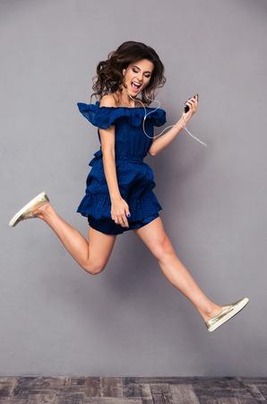 escucha activa: Retrato de cuerpo entero de una mujer divertida en traje de escuchar m�sica y saltando sobre bakground gris